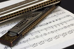 Two Harmonicas on sheet music royalty free stock image