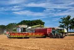 Two harvester unloading corn on tractor Royalty Free Stock Image