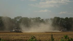 Two harvesters go on the field. In different directions from each other, collecting the wheat, the center of the frame wheat dust is a pillar, in the background stock video footage