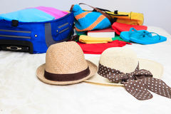Two hats and suitcase with clothing on bed in room Stock Photography