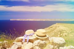 Two hats on vacation in mountains at the sea. Mountains vacation concept Stock Images