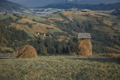 Two hay ricks in the countryside with mountains Stock Image