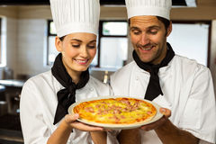 Two head chef presenting a pizza Royalty Free Stock Images