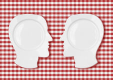 Two head plates face to face on red tablecloth. Two head plates face to face on red picnic tablecloth Royalty Free Stock Photography