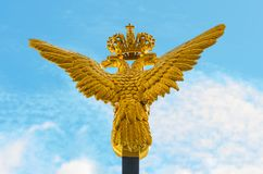 Two-headed golden eagle on blue sky background. Royalty Free Stock Image