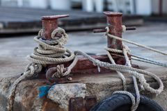 Two-headed mooring bitt wrapped with rope. Knecht on old pier. Two-headed mooring bitt wrapped with rope stock photo