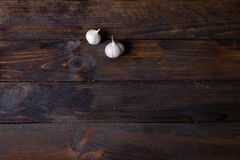 Two heads of garlic on wooden background. Two heads of garlic on dark wooden background Stock Image