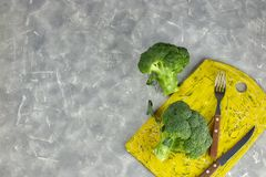 A couple of buds of healthy salad are on the yellow Board. fresh green broccoli. vertical kind of green vegetable flower. healthy stock images