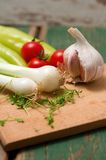 Two heads of spring onion on chopping board Royalty Free Stock Photo