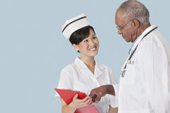Two health professionals having a discussion over medical report against light blue background Stock Photography