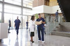 Two healthcare workers talk in the lobby of a busy hospital royalty free stock photo