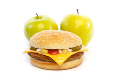 Two healthy apples behind a hamburger Royalty Free Stock Photography