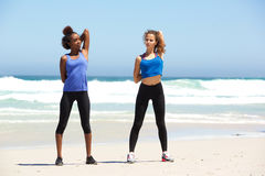 Two healthy young women stretching exercise at the beach Royalty Free Stock Images