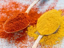 Two heaping scoops of spices of paprika powder and turmeric, cur Stock Photo