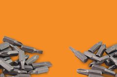 Two heaps of different interchangeable heads or bits for manual screwdriver for woodworking and metalworking on orange background. With copy space for your text stock photos
