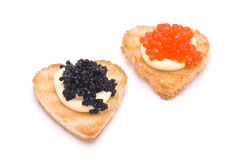 Two Hear-Shaped Toasts with Caviar. Two Hear-Shaped Toasts with Red and Black Caviar isolated on white Royalty Free Stock Photo