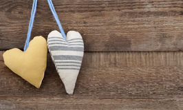 Two heart fabric on a background of the old wooden walls. Royalty Free Stock Photo
