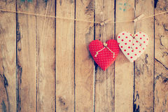 Two heart fabric hanging on clothesline and wood background with Stock Photo