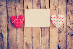 Two heart fabric and paper hanging on clothesline at wood backgr Royalty Free Stock Photography