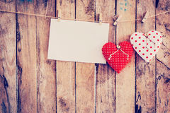 Two heart fabric and paper hanging on clothesline at wood backgr Royalty Free Stock Photo