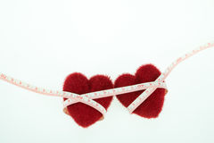 Two heart with measuring tape. In white background Royalty Free Stock Photography