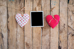 Two heart and photo frame hanging on clothesline rope with woode Stock Image