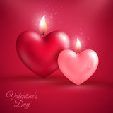Two heart shape candles on red background Royalty Free Stock Photo
