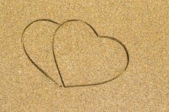 Two heart shape engraved in a wet sandy beach Royalty Free Stock Photo