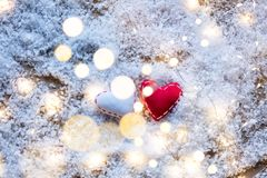 Two Heart shape toys and Fairy Lights on snow background Royalty Free Stock Photos