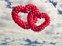 Two heart-shaped baloons in the sky, Royalty Free Stock Images