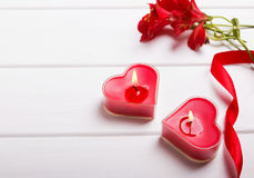 Two heart shaped candles, ribbon and red flowers Royalty Free Stock Images