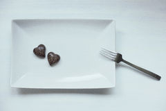 Two heart shaped chocolate pralines on a white plate Royalty Free Stock Images