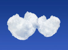 Two heart shaped clouds on blue sky background Royalty Free Stock Images