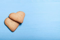 Two heart-shaped cookie on a blue wooden table Royalty Free Stock Photo