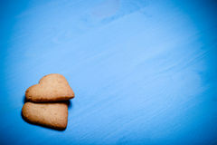Two heart-shaped cookie on a blue wooden table. Toned Royalty Free Stock Image