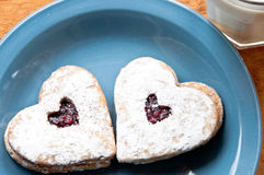 Two heart-shaped cookied on a blue plate with milk stock photography