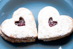Two heart-shaped cookied on a blue plate royalty free stock photography