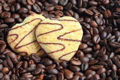 Two heart-shaped cookies on coffee beans stock image