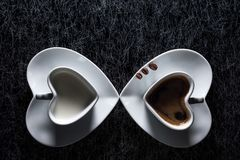 Two heart shaped cups with black coffee and milk pointing to each other, with three coffee beans Royalty Free Stock Photography