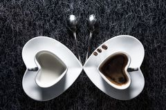 Two heart shaped cups with black coffee and milk pointing to each other, with three coffee beans royalty free stock images