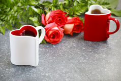 Two heart shaped cups with tea and bouquet of roses Royalty Free Stock Image
