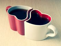 Two heart-shaped cups of tea on a wooden table royalty free stock photos