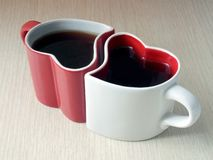 Two heart-shaped cups of tea on a wooden table stock photo