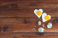 Two heart-shaped fried eggs on wooden background Royalty Free Stock Photos