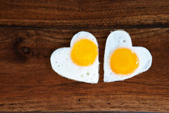 Two heart-shaped fried eggs on wooden background Royalty Free Stock Image