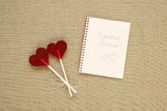 Two heart-shaped lollipops and a note Stock Photography
