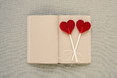 Two heart-shaped lollipops on an old diary Stock Photos