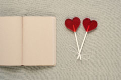 Two heart-shaped lollipops and an old diary Royalty Free Stock Photo