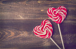 Two heart shaped lollipops for Valentine's Day. On the old wooden background. Vintage toned picture Stock Image