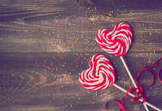 Two heart shaped lollipops for Valentine's Day. Two heart shaped lollipops with red ribbon for Valentine's Day on the old wooden background. Vintage toned Royalty Free Stock Image